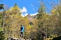 八ケ岳連峰の岩壁「大同心」を背に紅葉の中を進む登山者=16日、赤岳鉱泉近く