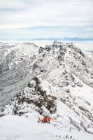 雪化粧した横岳(中央右)や硫黄岳(同左)。遠くに見える浅間山(右奥)も初冠雪となった=18日午前10時40分ごろ、赤岳山頂付近から撮影