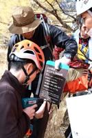 賽の河原分岐点手前に看板を設置する関係者