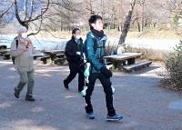 アシストロボットを装着し、上高地の河童橋周辺を歩く梅沢さん(右)=11日、松本市安曇