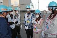 東京電力福島第1原発で、処理水が入った容器を手に取る在日台湾人の若者ら=18日午後、福島県大熊町