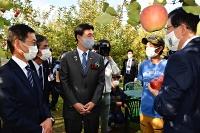 リンゴ畑で中村さん(右から2人目)と話す川勝知事(同1人目)や小岩副知事(左から3人目)ら