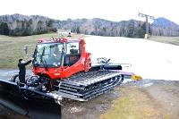 圧雪車で人工雪をならし、22日のオープンを目指す志賀高原の熊の湯スキー場=19日午後3時36分、山ノ内町