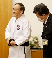 9段位の授与を受け、プレゼントされた道着と黒帯に着替える菅首相=20日午後、首相官邸(空手道マガジンJKFan提供)