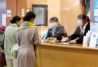 チェックインの混雑を避けるため車で待機していた客をフロントで迎える従業員=20日午後3時55分、阿智村の「癒楽の宿清風苑」