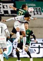 松本山雅―岡山 後半、自陣ゴール前で相手FWとボールを奪い合う松本山雅・橋内(中央上)