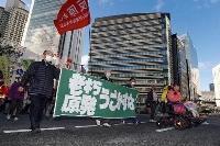 関西電力美浜原発3号機などの廃炉を訴え、大阪市内でデモ行進する市民団体のメンバーら=23日午後