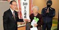 500万人目の入館者となり、記念品を受け取る小林さん(中央)