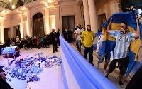 26日、アルゼンチン・ブエノスアイレスの大統領府で一般公開されたマラドーナさんのひつぎの前を通り過ぎるファンら(ロイター=共同)