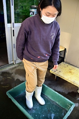 長靴の底を消毒する飼育員=26日、飯田市立動物園