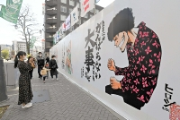 高橋ヒロシさんが描いた作品。メッセージを書いた松本蟻ケ崎高書道部の鍋田舞さん(左)が訪れ、スマートフォンで撮影した