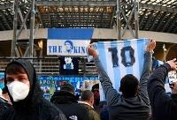 欧州リーグの試合が行われた競技場前に集まり、マラドーナさんの死を悼むナポリのファンたち=26日、ナポリ(ゲッティ=共同)