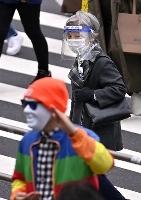 マスク姿で東京・新宿を歩く人。都内の新たな新型コロナウイルス感染者数が過去最多となった=27日午後
