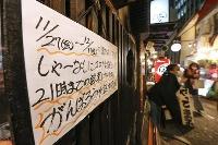 大阪・梅田の居酒屋に張られた時短営業のお知らせ。「しゃーなしにコロナ対策として21時までの営業。がんばろう北区、中央区」の文字に店主は「今の思いを込めました」と話した=27日夜