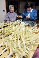 松子さん(左)が見守る中、「お神酒の口」を編む娘の恵利子さん