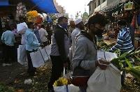 インド南部ベンガルールの市場でマスクを着けて買い物をする人々=20日(AP=共同)