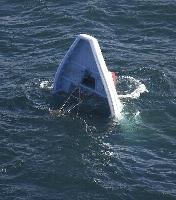 貨物船と衝突し転覆した遊漁船「第5不動丸」=28日午前9時49分、茨城県の鹿島港(共同通信社ヘリから)