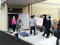 仮設校舎にあった棚などを本校舎(奥)に運び入れる豊野中の教職員ら