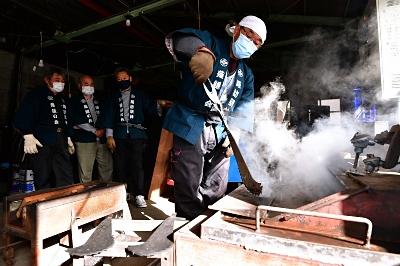 電気炉で熱した薙鎌を取り出す「薙鎌の会」の会員=29日午後1時15分、茅野市