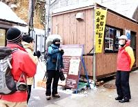 釜トンネル前で入山者に声を掛ける救助隊員(右)