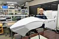 神戸社長が設計した電動のドローン(手前)。山小屋への荷物搬送を目指す機体は全長が約2倍になる見通しだ=昨年12月25日、小布施町