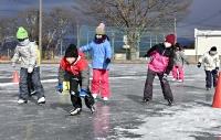 校庭リンクで初滑りを楽しむ原小学校の児童たち