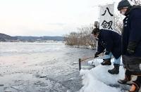 結氷した湖面から氷を切り出す氏子総代ら=10日午前6時53分、諏訪市の諏訪湖