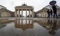 ドイツ・ベルリン中心部にあるブランデンブルク門の前を歩く人々=12日(AP=共同)