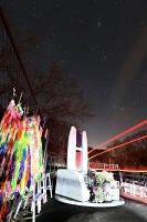 星空の下、通り過ぎる車のヘッドライトに照らし出された慰霊碑=14日午後6時51分、軽井沢町