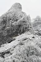 岩の黒と雪の白でまだら模様になった岩壁「大同心」=18日