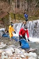 袋に詰めて粟沢川に浸したソバの実を引き上げる組合員ら