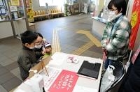 上田電鉄別所線へのメッセージを記す親子(左)