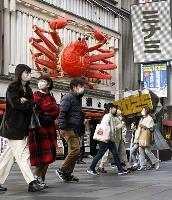 大阪・ミナミをマスク姿で歩く人たち=23日午後