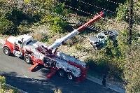23日、米ロサンゼルス近郊で事故を起こして大破し、つり上げられるウッズ選手の車両(AP=共同)