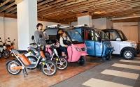 手前からミニバイク、開放型3輪、貨物型3輪、小型4輪と屋田社長(左)