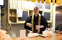 居酒屋のカウンターで客と話す青木さん