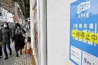 「一時停止中」のシールが貼られた「Go To トラベル」のチラシ=2020年12月、JR名古屋駅