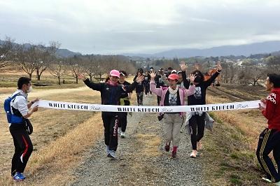 天竜川河川敷で笑顔を見せながらゴールする参加者=7日午前11時44分、飯田市