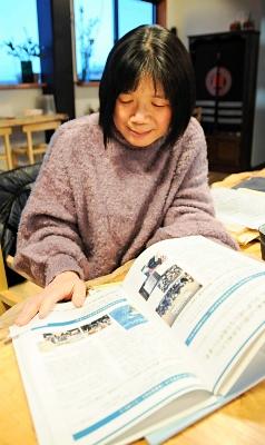大川小のシンポジウム資料を見て、佐藤さん夫妻との交流を振り返る山下さん=2月17日、安曇野市