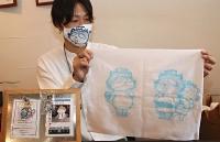 マスクを着け、手拭いを手にする峯村さん