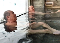 再開した千曲市の入浴施設「白鳥園」で間隔を空けて湯に漬かる来館者たち