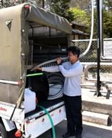 軽トラックの荷台に積んだタンクに温泉を入れる遠藤さん