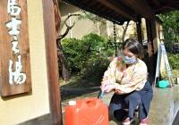 源泉の湯をタンクに詰める富士乃湯のおかみ