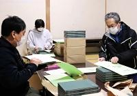 住民に配るため記録誌を封筒に入れる入沢災害復旧・復興協議会のメンバー