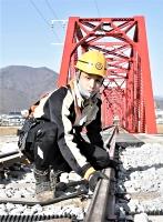 28日の全線開通に向け、千曲川橋梁(後方)近くのレールを確認する市村さん=17日