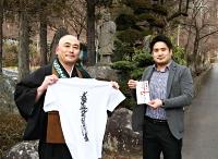 播隆上人像の前で荻須さん(左)から受け取った寄付金を手にする穂苅さん