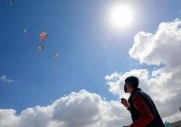 25日、パレスチナ自治区ガザ南部ハンユニスで、空高くたこを揚げる生徒(パレスチナ難民救済事業機関提供、共同)