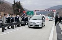 宮古盛岡横断道路が全線開通し、通り初めをする車両=28日、岩手県宮古市