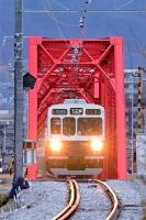 上田駅を出発し、千曲川橋梁を渡る別所線の「1番列車」=28日午前5時56分、上田市諏訪形