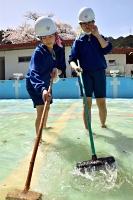 プールの中に入り、ブラシがけをする天龍中の生徒たち=29日、天龍村